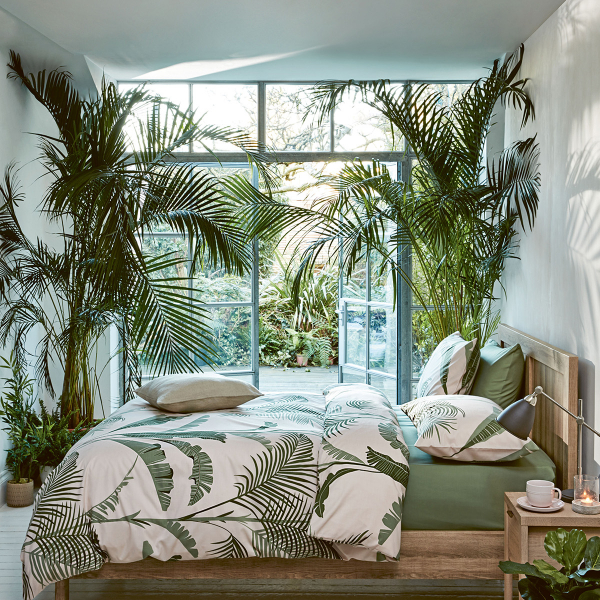 Looking at the soft tropics trend, Sophie Robinson advises to invite nature inside with living plants and go for it in volume to create a really dramatic lush look. A large palm print bedlinen can add to the drama. #bedroom #palmprint #sophierobinson #softropics