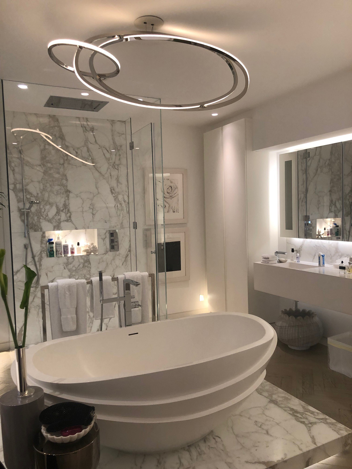 Kelly Hoppens' master bedroom ensuite complete with a sculptural bath tub, huge statement pendant light and his and hers basins. The house tour was part of the Great Indoors podcast with Sophie Robinson and Kate Watson-Smyth. #sophierobinson #kellyhoppen #bathroom #bathroomlight