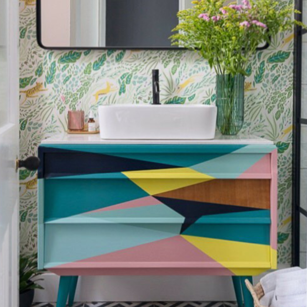 The overall winner in the Anglian Styled By Me Competition. Judge Sophie Robinson loves patterned wallpaper in a small bathroom, as it adds a splash of character and interest. The painted basin unit is a unique design featuring an abstract painted effect taking inspiration from the colours in the wallpaper. #bathroomdesign #paintedunit #sophierobinson