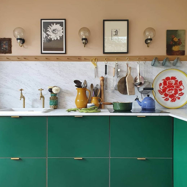 An instant update to the Ikea kitchen - Plykea supply plywood doors and worktops for Ikea kitchens and these bold green doors sit perfectly with the peach walls. For a practical touch a handy peg rail is used for a variety of utensils. #plykeakitchens #colourfulkitchens #sophierobinson