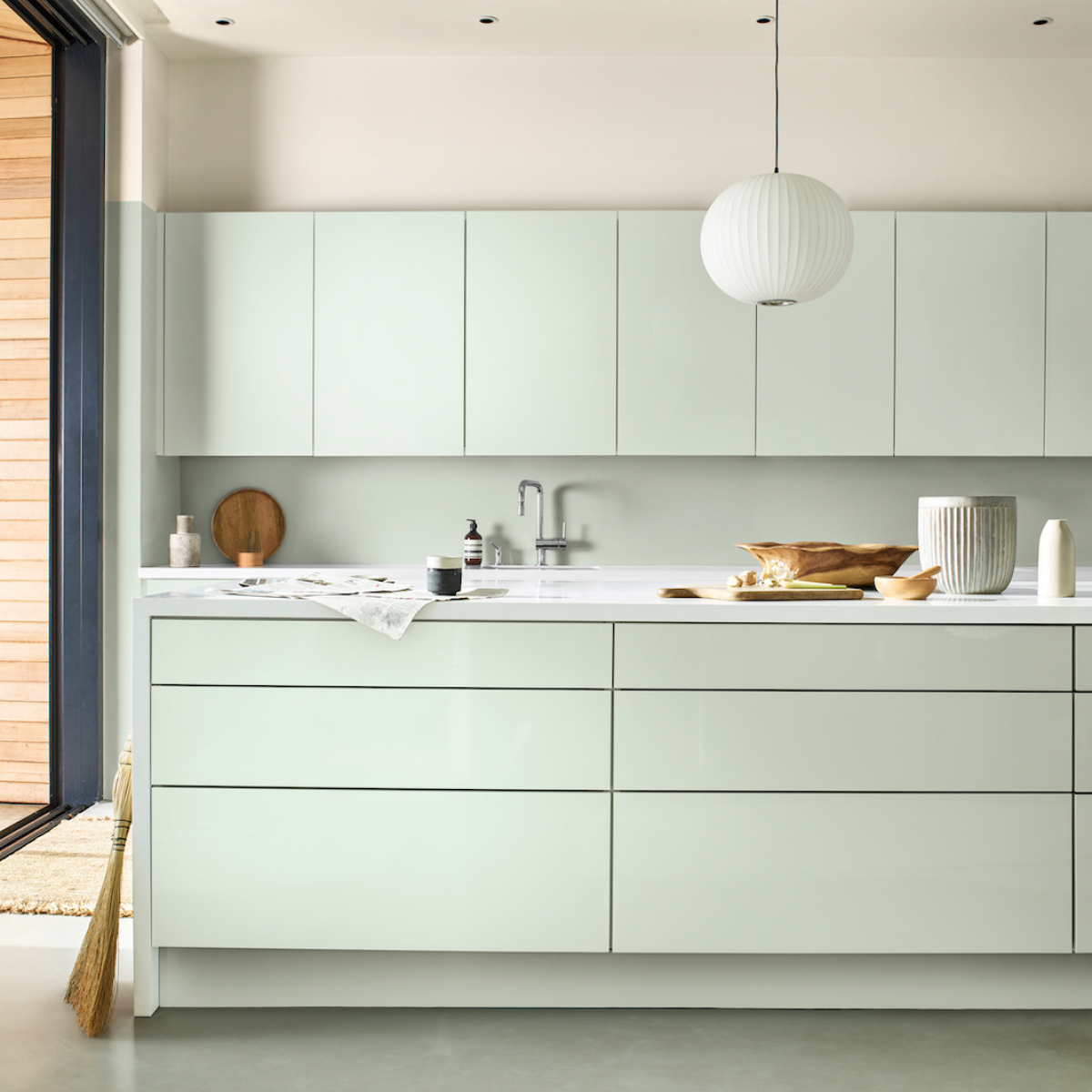 The Dulux Colour of the Year has been announced as Tranquil dawn. A soft, grey-green whihc is aimed to create a feeling of calm, is a versatile choice on a modern kitchen and works well with the black sliding patio doors. #dulux #sophierobinson #tranquildawn