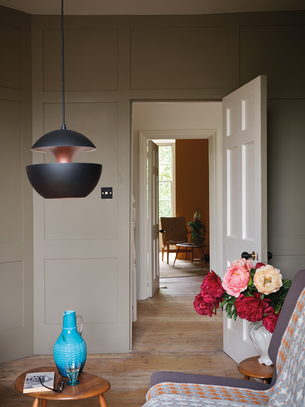 Contemporary lighting and accessories sit happily with the classic panelled wall is painted in Broccoli Brown, one of the new Farrow & Ball and Natural History Museum new colours. Sophie Robinson looks at the new paint collection here. #farrowandball #panelledwall #livingroom #sophierobinson