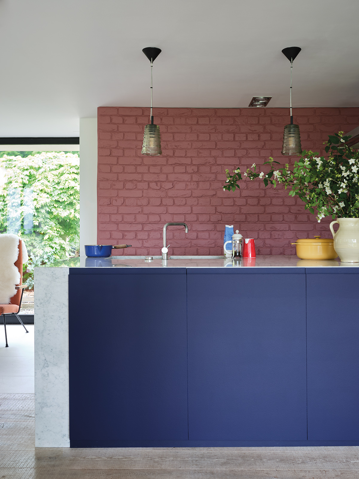 The strong pigment shows in this intense shade of blue on kitchen cabinets, it creates a welcoming feel against the bare red brick wall. Just one of the new paint collection by Farrow & Ball and The Natural History Museum. Interior designer Sophie Robinson takes a look through the whole collection here. #farrowandball #bluekitchen #barebrick #sophierobinson