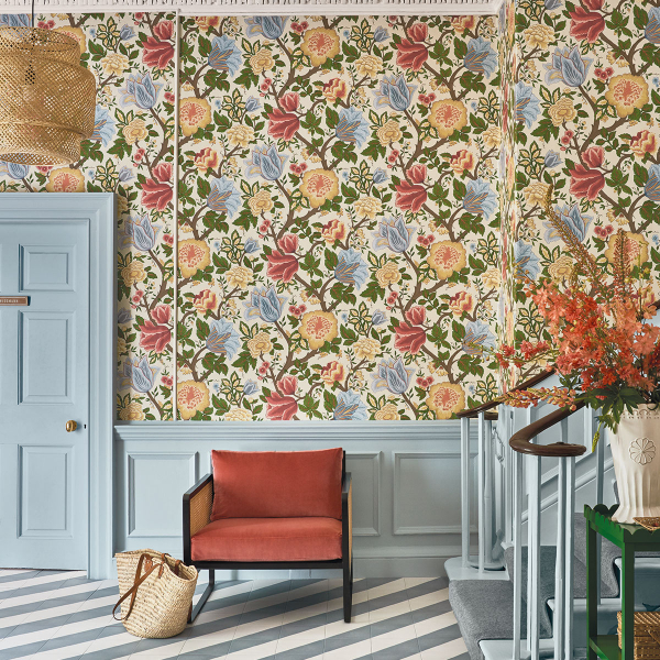 Interior designer and colour lover Sophie Robinson shares some top tips on how to use wallpaper. In this entrance hall a classic floral design is combined with pale blue panelling and a modern diagonal striped tiled floor. #entrancehall #sophierobinson #panelling