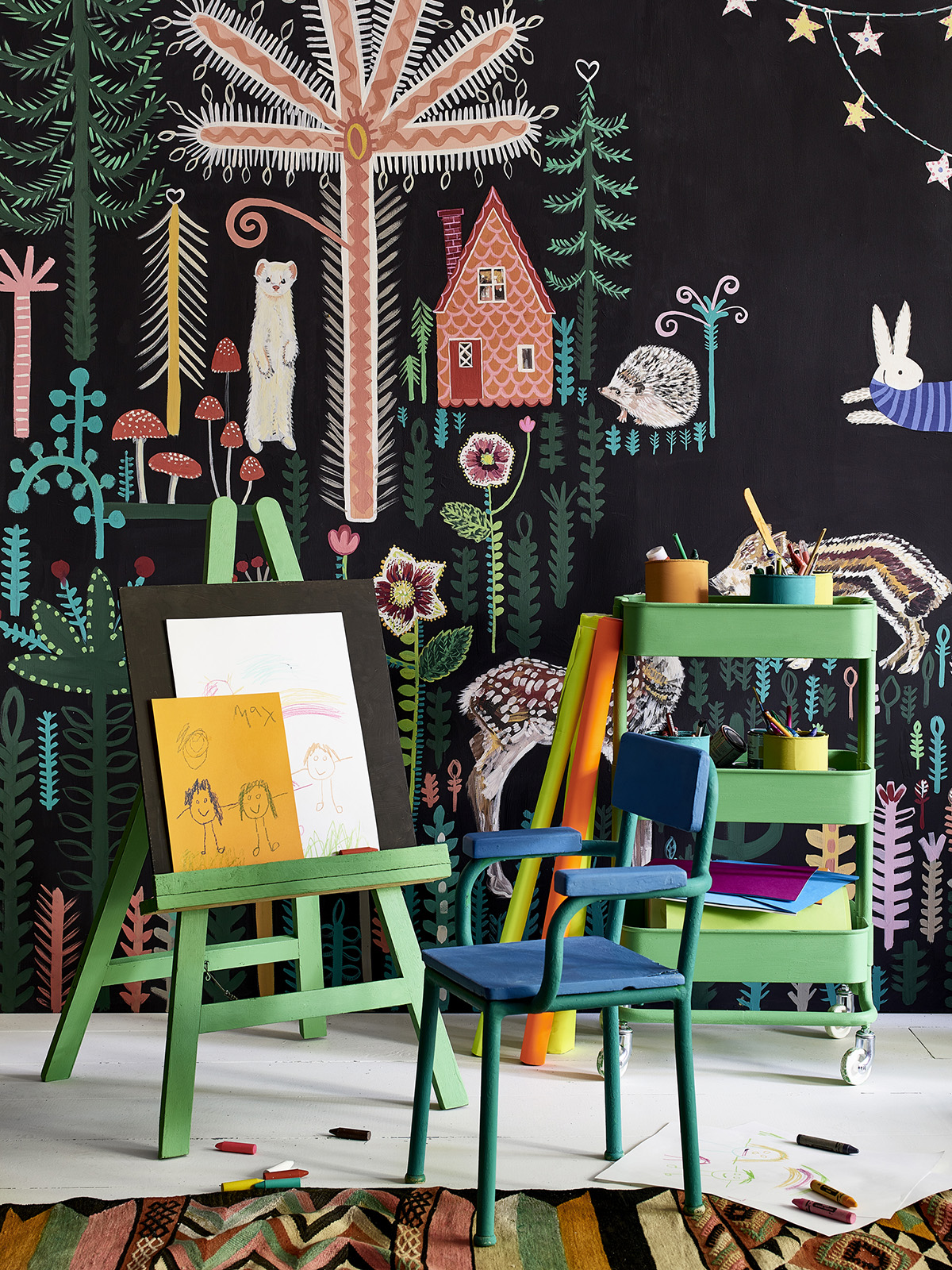 Kids painted mural with black background and brightly coloured motifs by Lucy Tiffney and brightly painted kids furniture by Annie Sloan