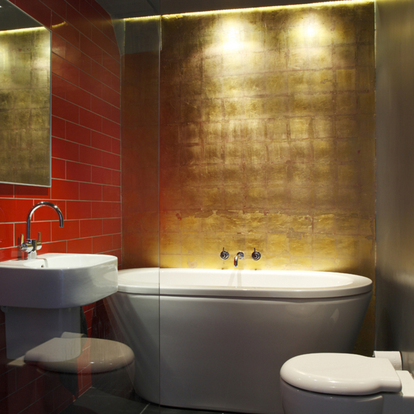 Freestanding modern bath with gold and red metro brick walls.