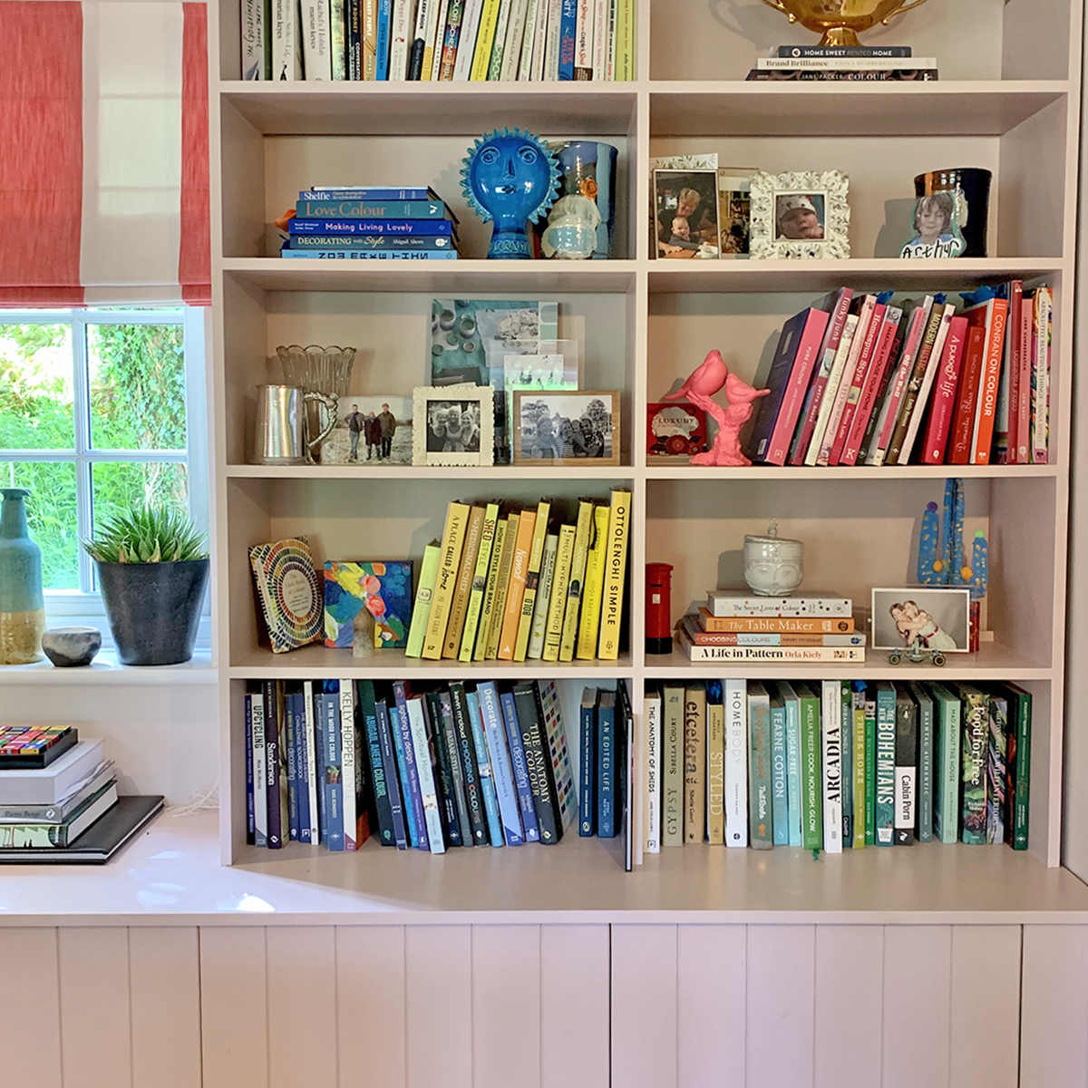 open bookshelves in pale pink with colour coded books and objets.