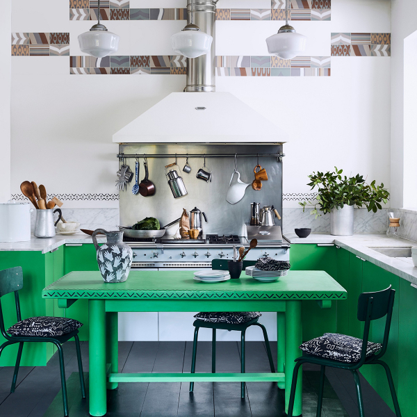 Bright green painted kitchen cabinets and large green dining table by Annie Sloan
