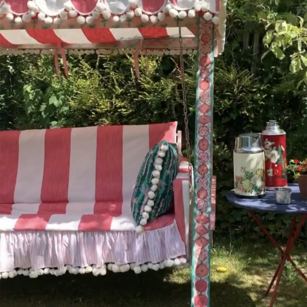 An ordinary garden swing seat is given an update with a red and white striped seat cover, pom pom tassels and fringing.