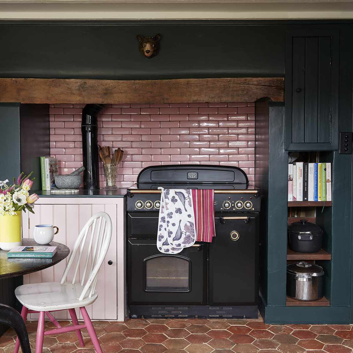 Sophie Robinson's kitchen with hexagonal terracotta floor tiles pale pink metro tiled splashback and white kitchen chair with pink legs