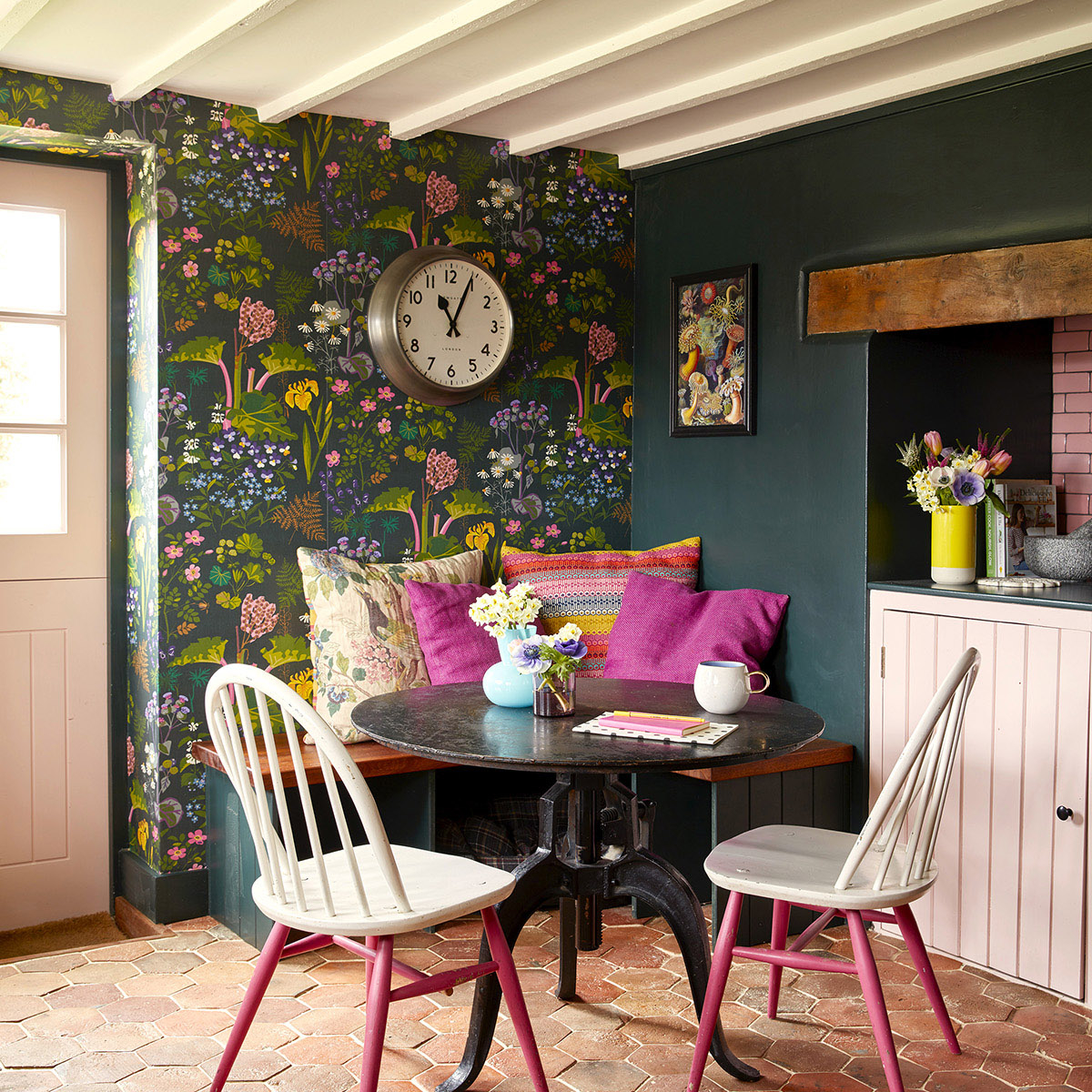 Sophie Robinson's kitchen seating corner. white dining chairs with pink legs, colourful patterned cushions and colourful botanical wallpaper