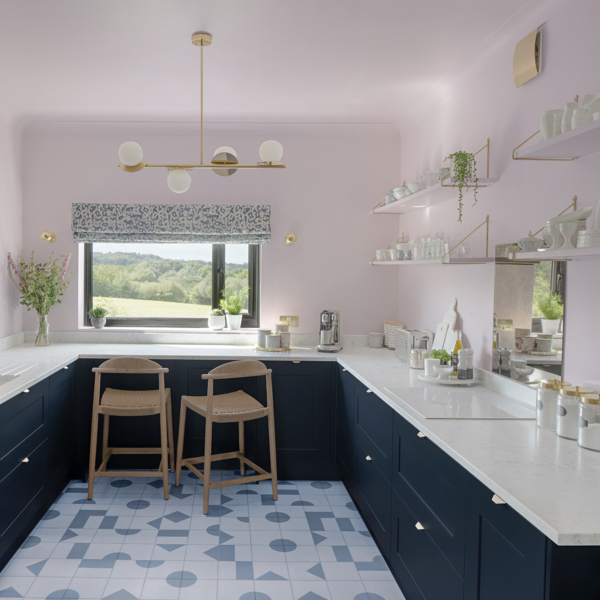 Kitchen renovation. Pale pink walls and ceiling, pale blue and white geometric floor, navy Howdens units and open shelving.