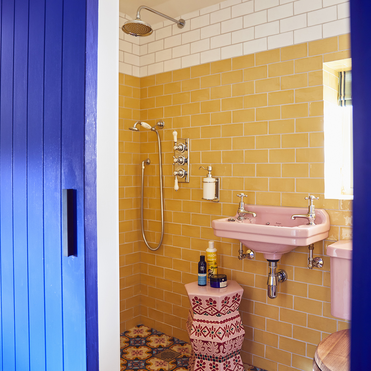 Shower room with yellow wall tiles, pink blue and yellow floor tiles and pink sanitaryware. In the home of Sophie Robinson