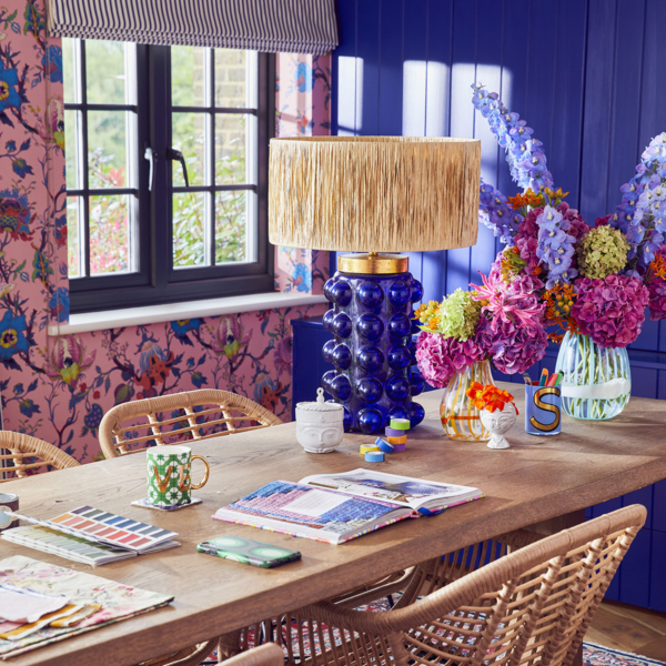 bold pink floral wallpaper, cobalt blue cupboards and wooden dining table with rattan chairs. Sophie Robinson's home office
