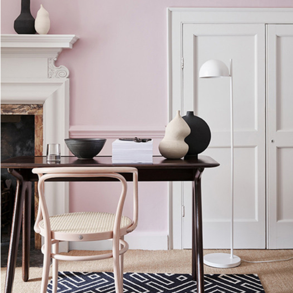 Pale pink walls, white floor lamp, black desk, pale wood chair and monochrome geometric rug. Image by Little Greene