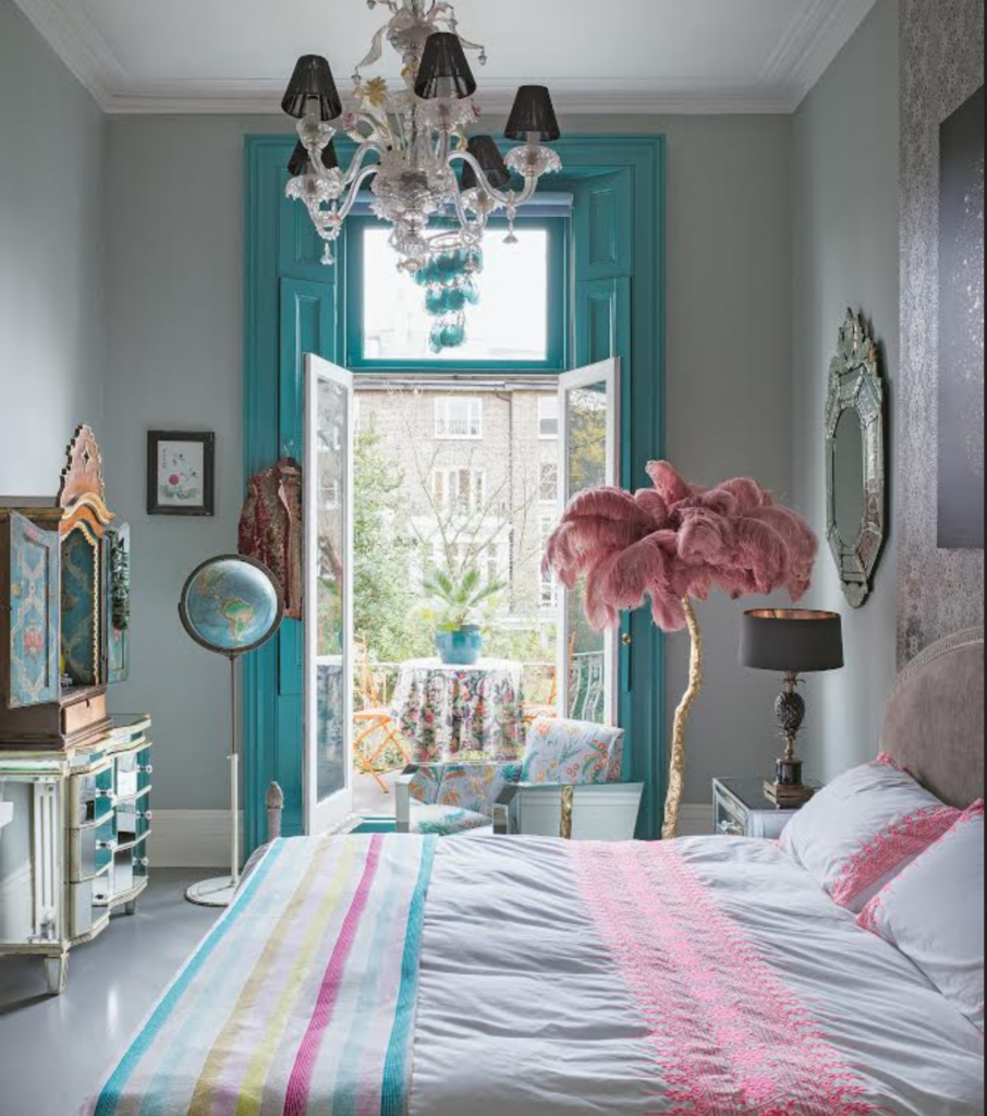 blue painted window shutters, pink feather floor lamp, mirrored furniture white and pastel striped bedlinen in the home of Matthew Williamson