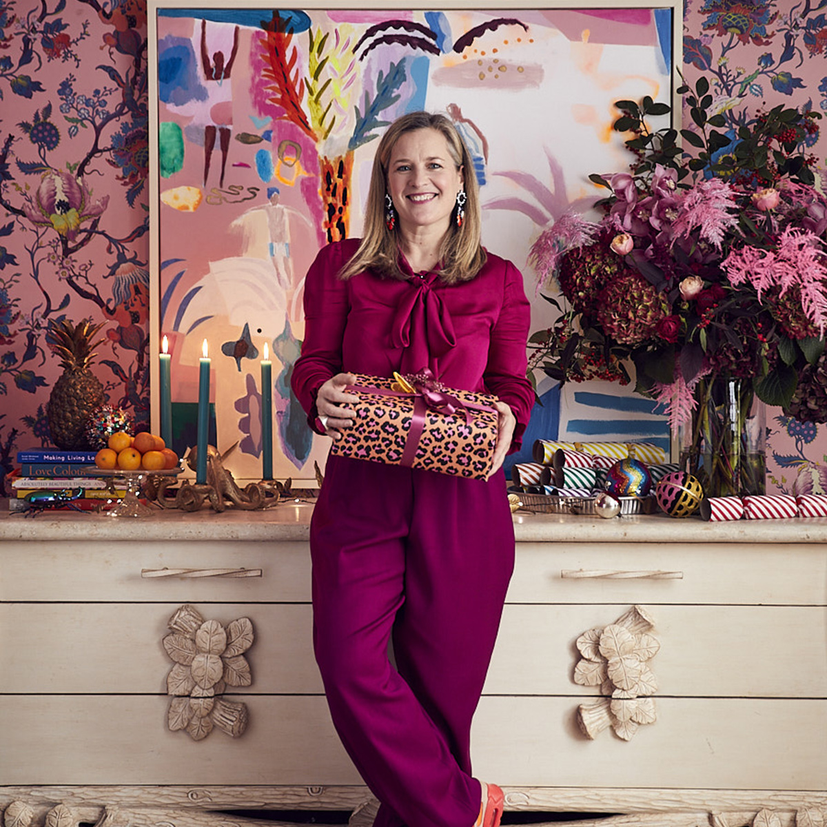 Sophie Robinson holding Christmas gift in front of her vintage sideboard, pink flraal wallpaper and large pink patterned abstract artwork