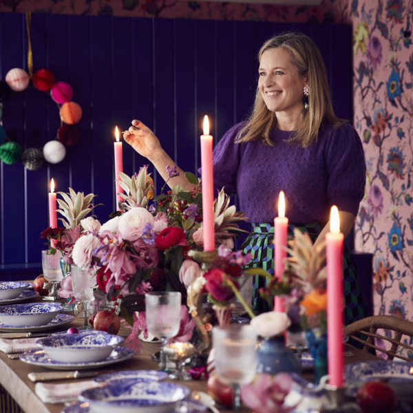 Sophie Robinson lighting the pink dinner candles on her Christmas large wooden dining table. With cane dining chairs on a traditional patterned rug, blue storage cupboards and pom pom Christmas wreath.