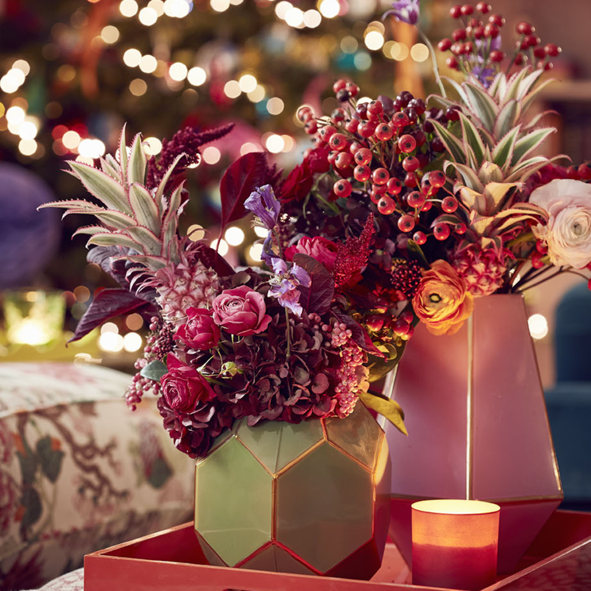 Red tray with green geometric vase and red theme floral display with pineapple tops and berries and Christmas tree in the background. Sophie Robinson's living room