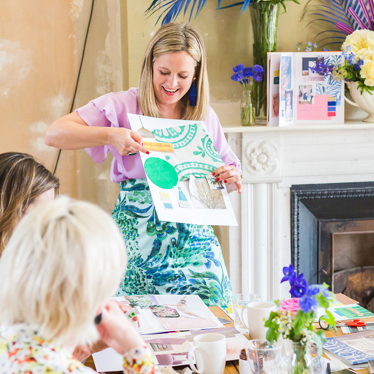 Interior designer Sophie Robinson showing a moodboard on her workshop. Distressed walls, large leaves and flowers in bright colours