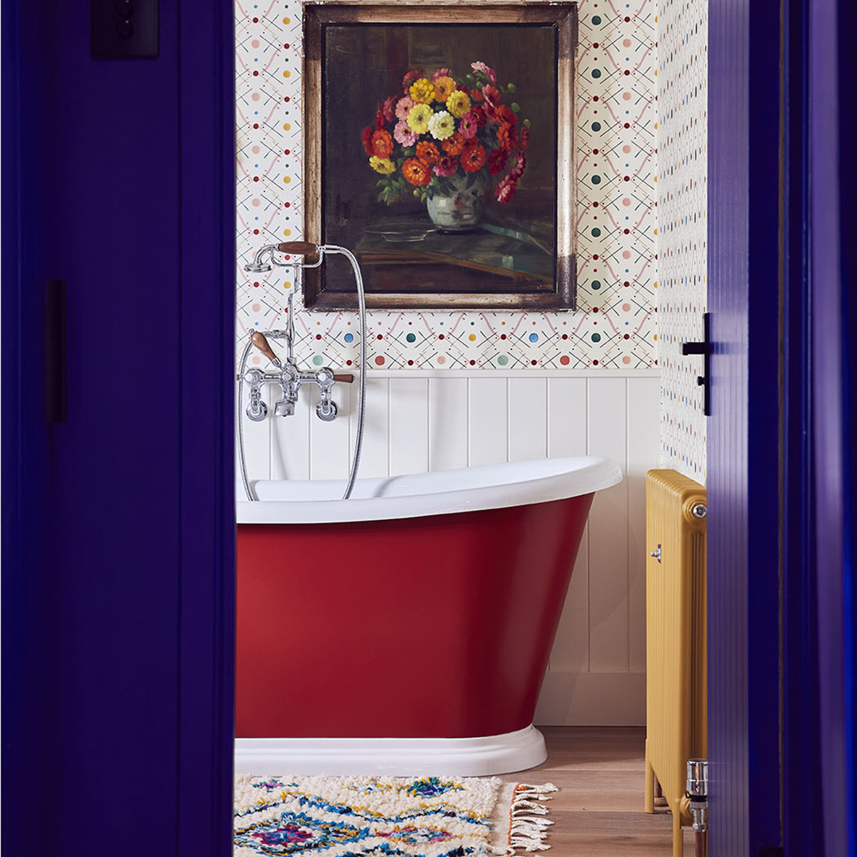 Looking through cobalt blue door and frame to red roll tap bath vintage framed art and yellow radiator in the bathroom of Sophie Robinson