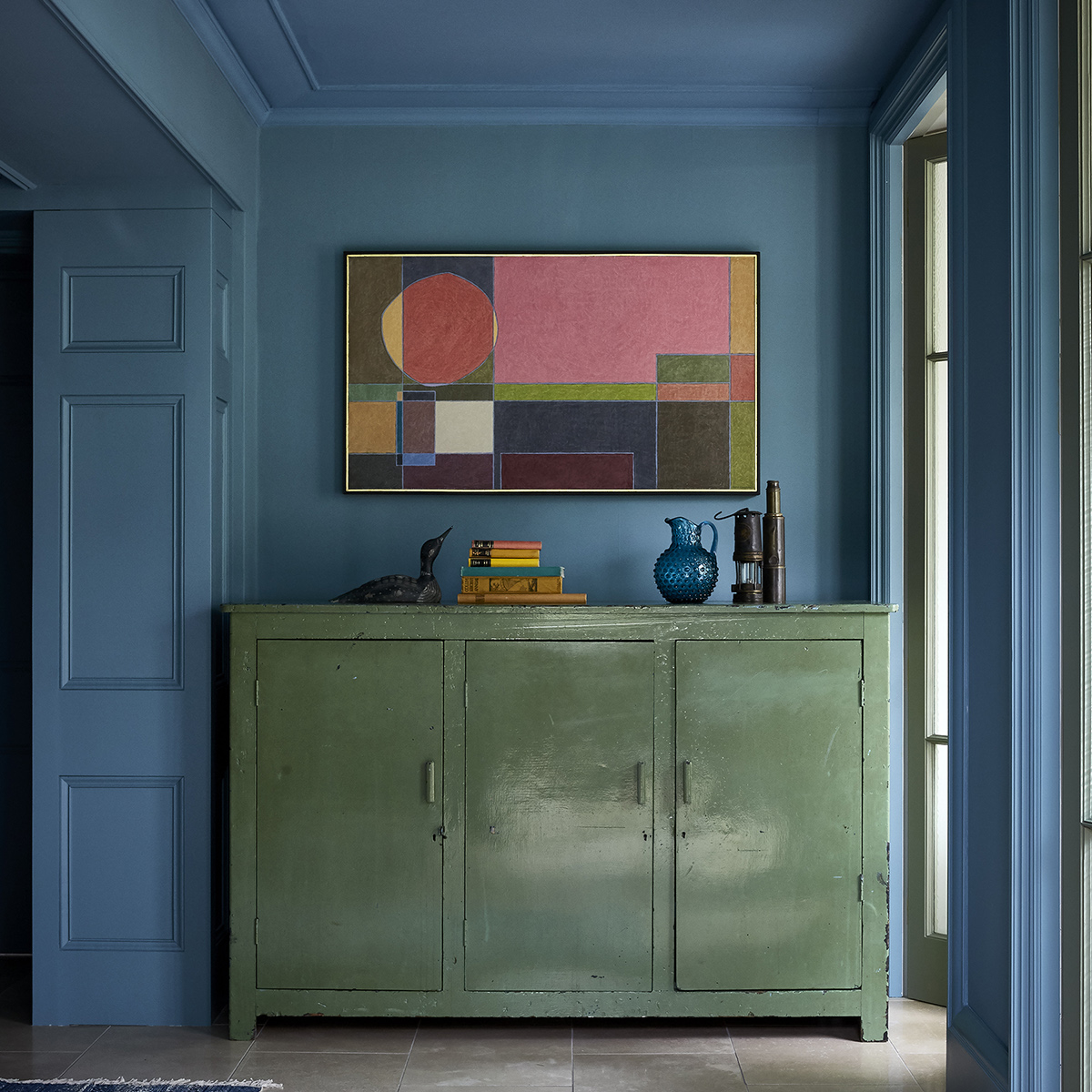 Blue walls and ceiling, high green lacquer sideboard with colourful geometric artwork. Design by Nicola Harding