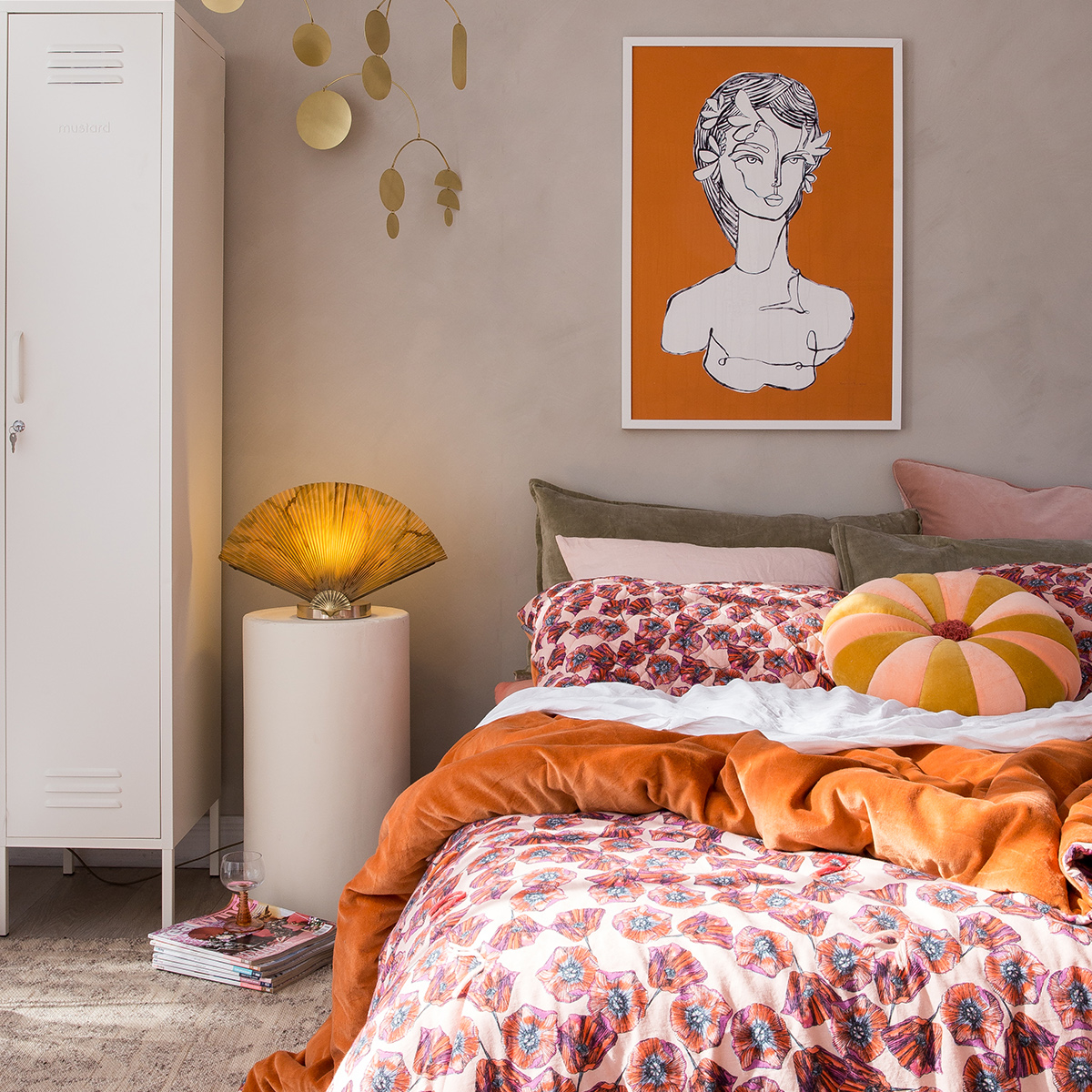 Bedroom with industrial style wardrobe, orange artwork and orange patterned bedding. From The New Mindful Home interior book by Joanna Thornhill