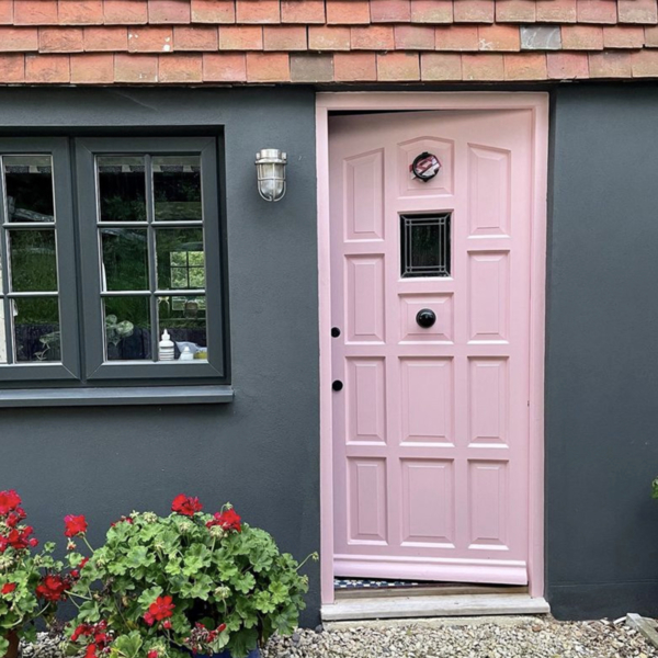 Sussex farmhouse exterior, black render, pale pink front door - the home of Sophie Robinson